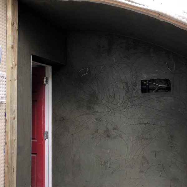 Render applied over cavity drain membrane